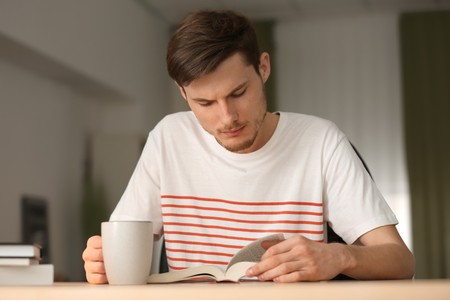 Young man reading book at home Stock Photo