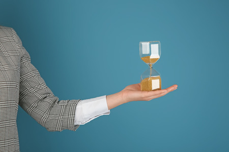 Woman holding hourglass on color background. Time management concept 스톡 콘텐츠