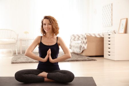 Beautiful woman practicing yoga in morning at home