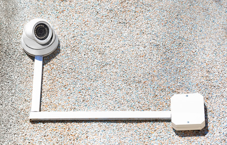 Modern CCTV camera installed on wall of building outdoors Stock Photo