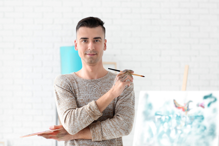 Male artist with paintbrush and palette in workshop 版權商用圖片