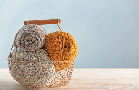 Basket with knitting yarn on table against color background