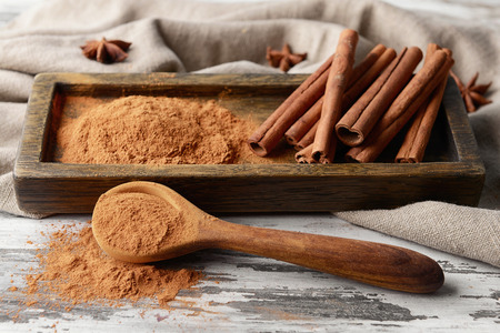 Composition with cinnamon powder on wooden background