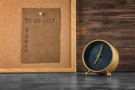Alarm clock on table and sheet of paper with to-do list on board. Time management concept Stok Fotoğraf