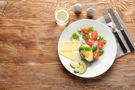 Plate with eggs baked in avocado and fresh vegetables on wooden table