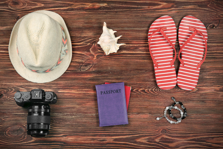 Composition with tourists stuff on wooden background, top view