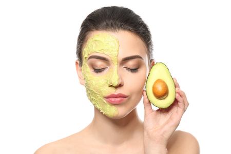 Beautiful young woman with facial mask and fresh avocado on white background