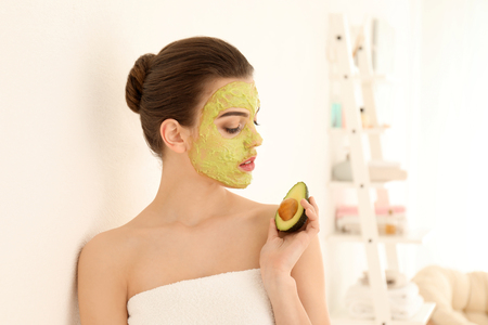 Beautiful young woman with facial mask and fresh avocado at home Standard-Bild - 113479278