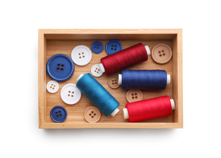 Wooden box with threads and buttons on white background