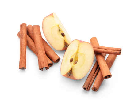 Pieces of fresh apple and cinnamon sticks on white background Imagens