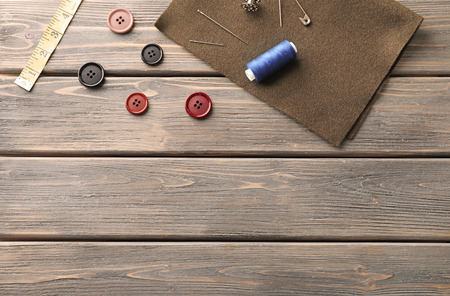 Fabric and sewing accessories on wooden background