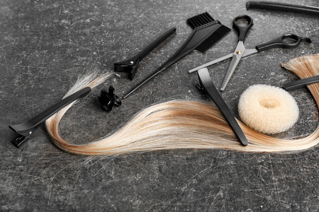 Professional hairdresser's set with strand of blonde hair on grey background