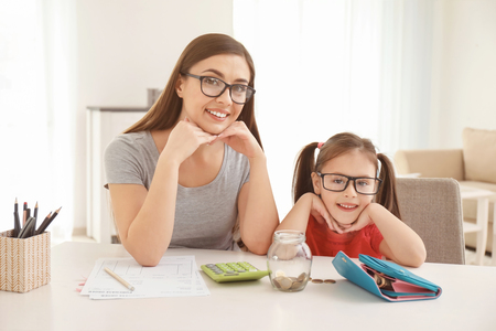 Happy little girl with her mother sitting at table indoors. Money savings concept Stock Photo