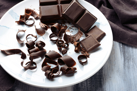 Plate with delicious chocolate curls on table