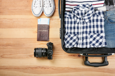 Tourists stuff and clothes with open travel suitcase on wooden background