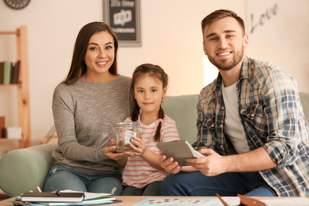 Happy family counting money indoors. Money savings concept Standard-Bild