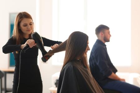 Professional hairdresser working with client in salon 版權商用圖片