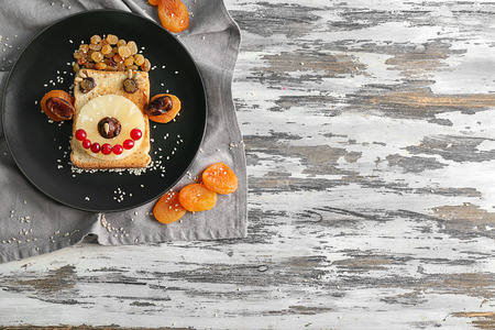 Plate with creative toast for child on wooden table