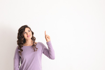 Beautiful young woman with raised index finger on light background