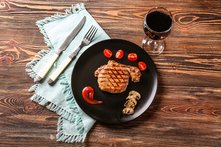 Plate with delicious grilled steak and glass of red wine on table Standard-Bild - 113590343