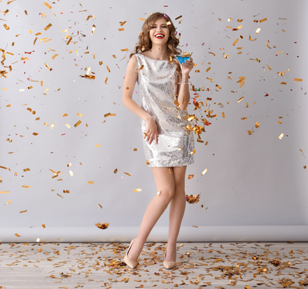 Beautiful young woman with drink and falling confetti on grey background