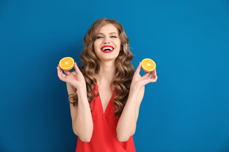 Beautiful young woman with halves of orange on color background
