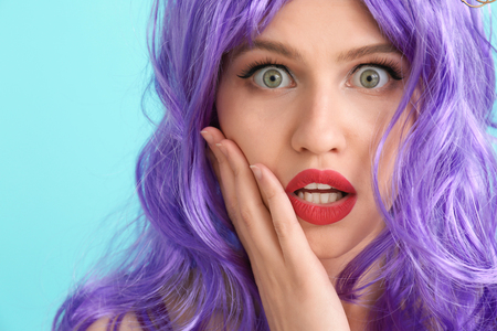 Shocked young woman with unusual hair on color background