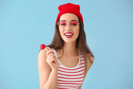 Attractive young woman with lollipop on color background Stock fotó