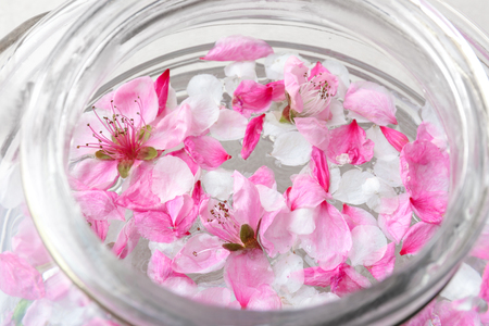 Glass jar with water and blooming flowers, closeup