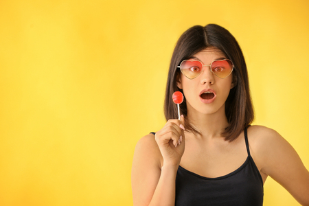 Beautiful young woman with lollipop on color background