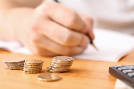 Młody mężczyzna liczy pieniądze przy stole, zbliżenie