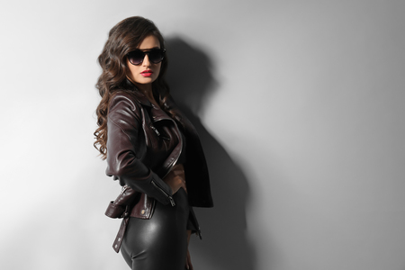 Beautiful young woman wearing leather clothes on grey background