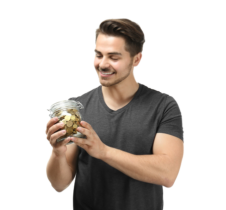 Young man holding glass jar with coins on white background. Savings money concept
