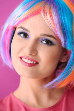 Extravagant young woman on color background, closeup