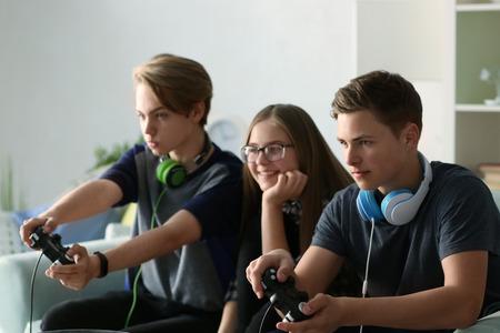 Adolescents jouant à des jeux vidéo à la maison