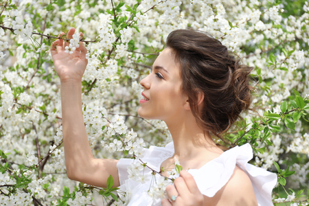 Beautiful young woman near blossoming tree on spring day