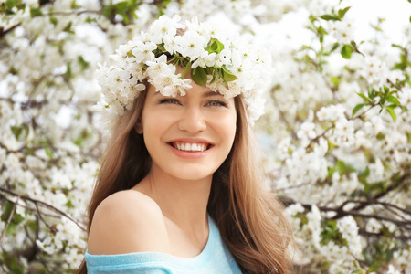 Beautiful young woman wearing flower wreath outdoors on spring day Stock Photo