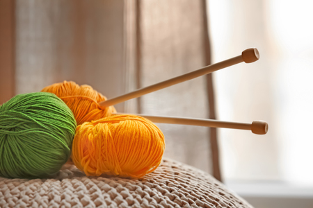 Colorful knitting yarns and needles on pouf indoors Stok Fotoğraf