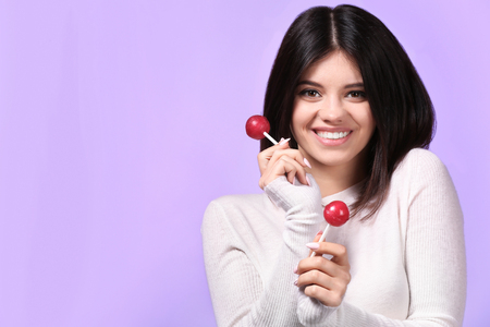 Beautiful young woman with lollipops on color background