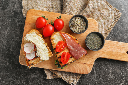 Toasted bread with vegetables and meat on wooden board