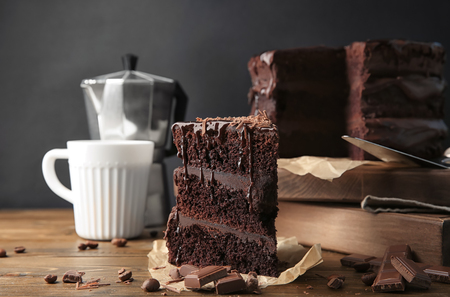 Piece of tasty chocolate cake on wooden table