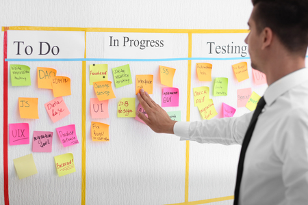 Man near scrum task board with stickers in office