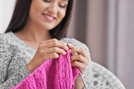 Young woman knitting warm sweater indoors, closeup