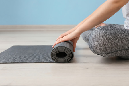 Young woman with yoga mat indoors