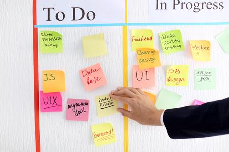 Hombre adjuntando una nota adhesiva al tablero de tareas scrum en Office