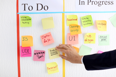 Man attaching sticky note to scrum task board in office Stock fotó
