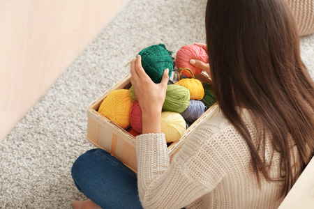 Young woman sitting on carpet and choosing color of knitting threads indoors