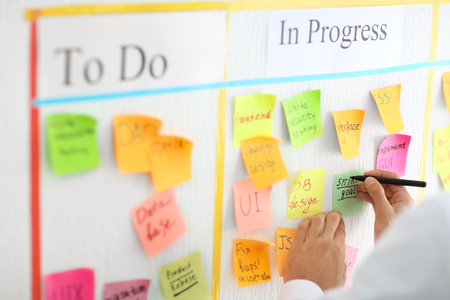 Man writing on sticky note attached to scrum task board in office Stockfoto