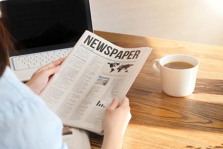 Giovane donna che legge il giornale a tavola al chiuso Archivio Fotografico