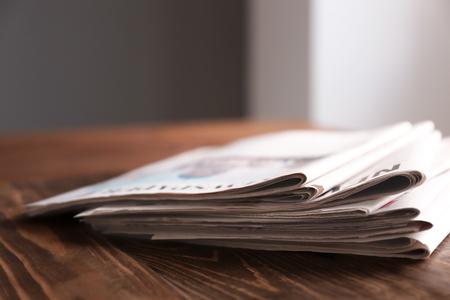 Pila di giornali sul tavolo di legno